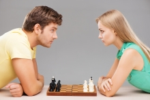 Serious young man and woman starting chess game and looking at each other